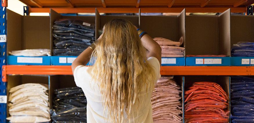 Employee getting shirt from warehouse